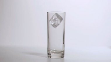Glass in super slow motion receiving an ice cube — Stock Video