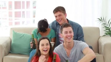 Smiling friends looking at the television while laughing — Stock Video
