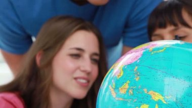 Smiling students looking at the world on a globe — Stock Video