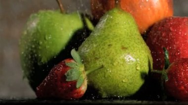 Rain falling in super slow motion on fruits — Stock Video