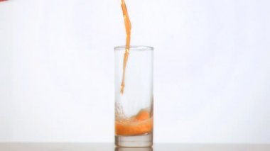 Fizzy orange juice poured in super slow motion in a glass — Stock Video