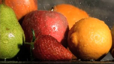 Rain falling in super slow motion on many fruits — Stock Video
