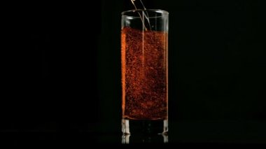 Amber fizzy drink poured in super slow motion in a glass — Stock Video