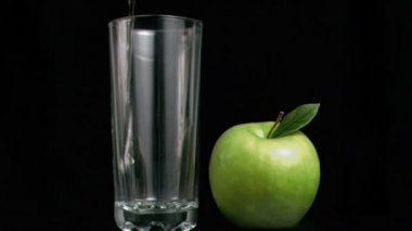Fresh apple juice flowing in super slow motion in a glass — Stock Video