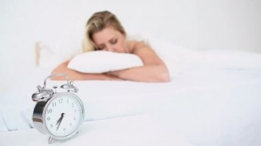 Alarm clock ringing while a woman sleeps — Stok video