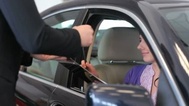Woman in her car signing a document in a garage