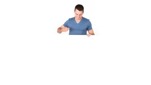 Hombre casual feliz apuntando a una tabla — Vídeo de stock