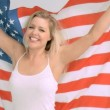 Smiling woman in slow motion holding the American flag - Stock Photo