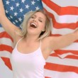 Blonde woman in slow motion holding the American flag - Stock Photo