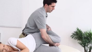 Physiotherapist manipulating the thigh of his patient — Stock Video