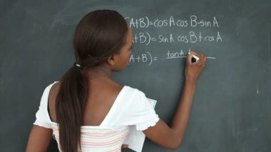 Video of a black student writing on a blackboard — Stock Video