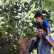 Son playing on shoulders of his father - Stock Photo