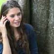 Stock Video: Womcalling leaning against tree