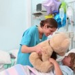 Smiling nurse showing a teddy bear to a child — Stock Video