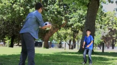 Father and his son playing football in a park — Stock Video