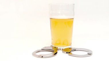 Car keys falling in a glass full of beer surrounded by cuff — Stock Video