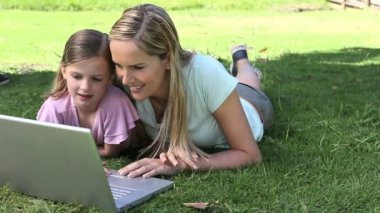 Mother and his daughter using a laptop in a park — Stock Video