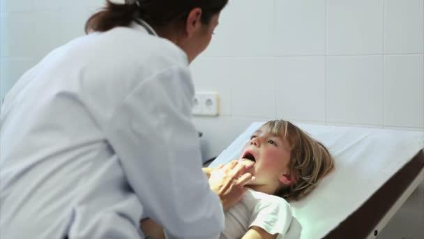 Doctor auscultating la boca de un niño — Vídeo de stock
