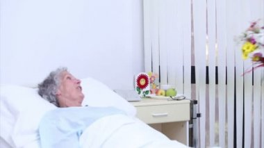 Serene senior woman speaking at a nurse who gives a bouquet of flowers — Stock Video