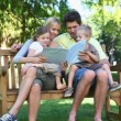 Family sitting on a bench reading a book - Foto Stock