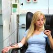 Blood donor looking at her mobile phone - Foto de Stock