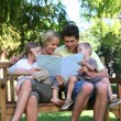 Family reading a book while sitting on a bench - Foto Stock