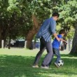 Son and his father playing football in a park - Foto Stock