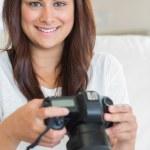 Brunette woman holding digital camera — Stock Photo #23045142