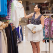Woman holding white shirts on hangers — Stock Photo #23045198
