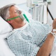 Stock Photo: Patient is lying in bed reading in hospital ward