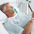 Patient is lying in bed reading in hospital ward - Stock Photo