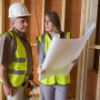 Woman and man discussing blueprints - Stock Photo