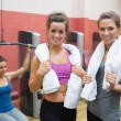 Two women with towels with woman using weight machine - Stock Photo