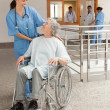 Nurse laughing with old women sitting in wheelchair — Stock Photo