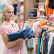 Woman standing holding pants — Stock Photo #23045980