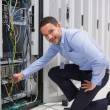 Technician plugging cable into server - Stock Photo