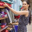 Woman putting jumpers on shelf and smiling — Stock Photo
