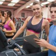 Gym Instructor and woman in the gym - Stock Photo