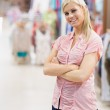 Woman standing in a shop arms crossed — Stock Photo