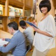 Woman holding tablet pc in library — ストック写真