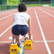 Stock Photo: Woman at starting blocks on track