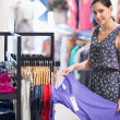 Woman holding purple shirt in clothes store — Stock Photo