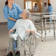 Nurse smiling at old women sitting in wheelchair — Stock Photo
