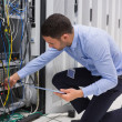 Man checking tablet pc as he is plugging cables into server - Stock Photo