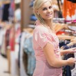 Woman  standing at the clothes rack and smiling - Foto Stock