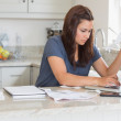 Woman holding a bill while calculating — Stock Photo #23046890