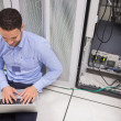 Stock Photo: Technicityping on laptop in front of server