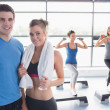 Woman and trainer smiling together in front of aerobics class — Stock Photo