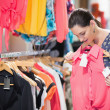 Woman looking at pink shirt - Foto Stock