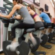 Four riding exercise bikes — Stock Photo #23047212